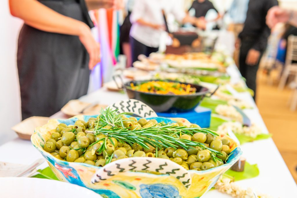 Olives in a colourful bowl with other dishes of food out of focus on a long table behind