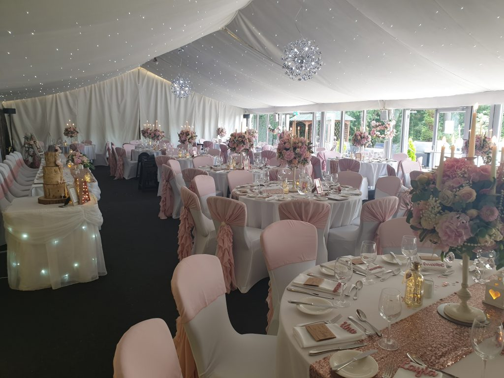 Inside a marquee with lots of fabric, table cloths, napkins and chaire covers