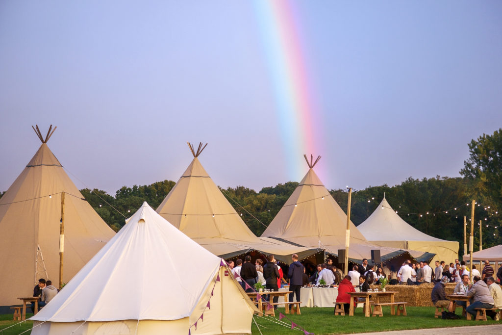 teepees and bell tents with a rainbow