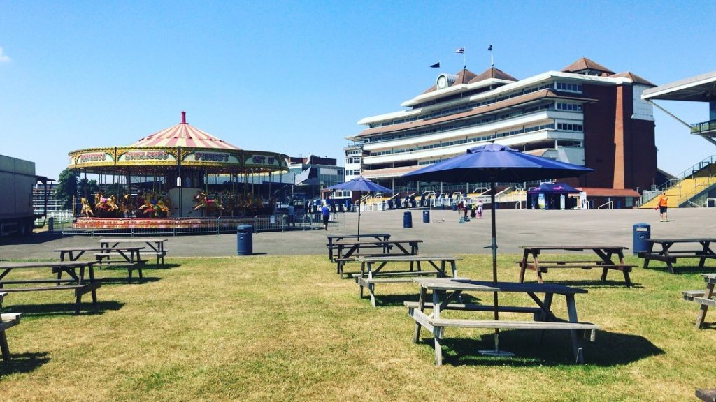 Buildings, carousel and picnic tables with parasols