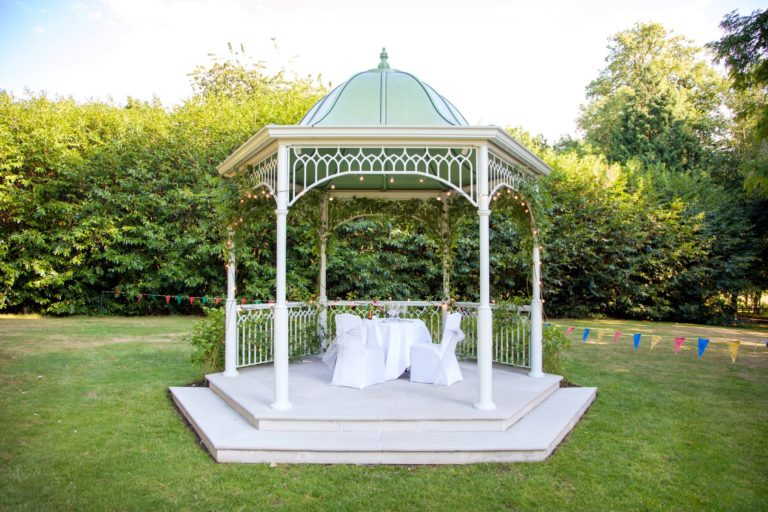 Pretty pergola on grass with bushes in the background