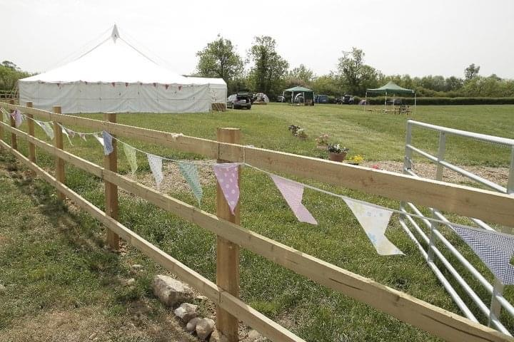 Fence with bunting and a lare white tipi in a field