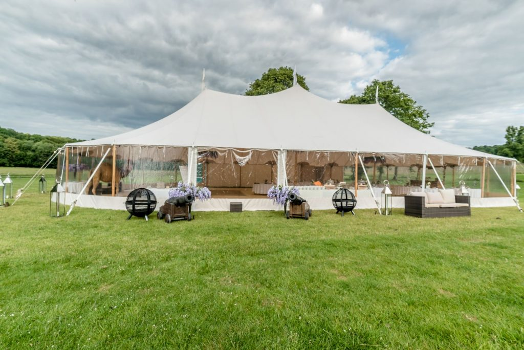 Big top cream marquee on green grass with a cloudy but blue sky
