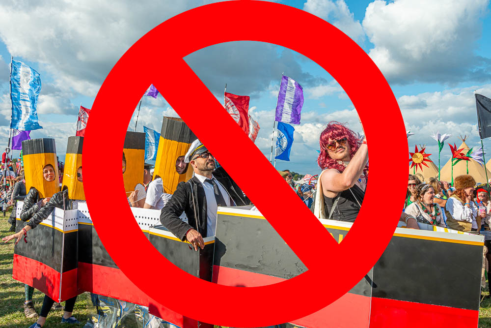 Festival goers in fancy dress in a cardboard titanic with a big red no entry sign over the top