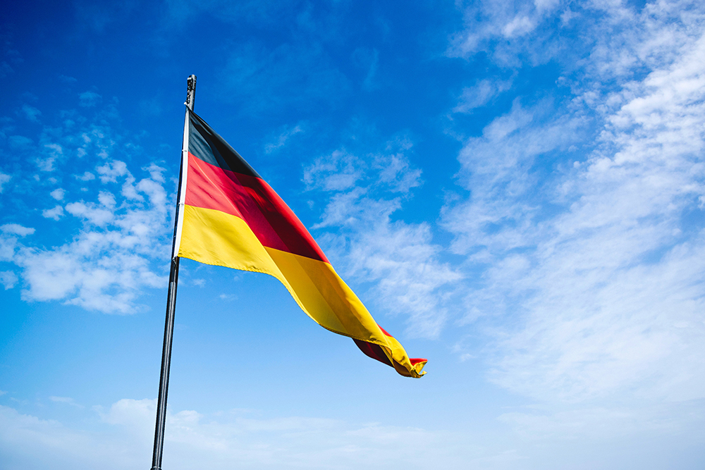 the german flag, black, red and yellow against a blue cloudy sky