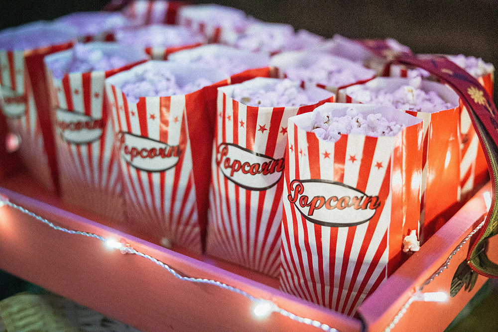 Popcorn in red and white striped paper bags with popcorn written on them