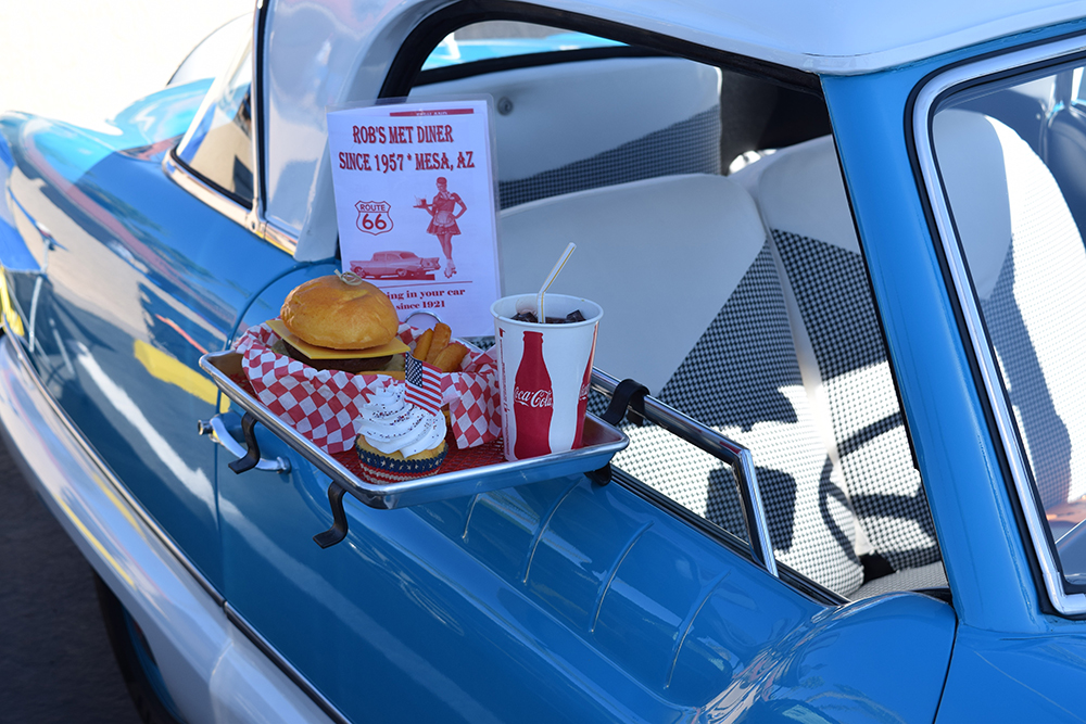 Drive-in hamburger meal clipped to the lowered side window of a blue car