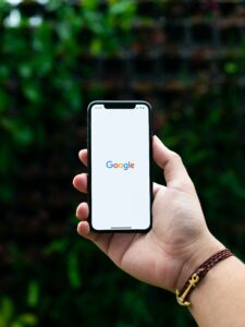 Google logo on a smart phone in someones hand