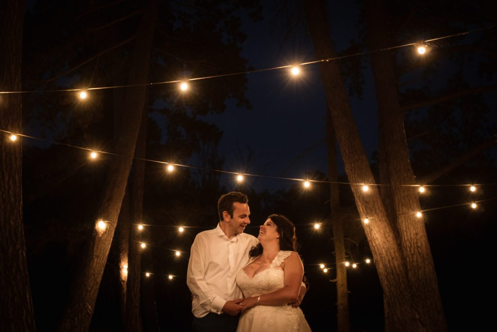 Newly wed couple in white at night under strings of lights