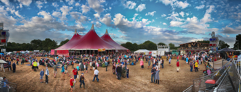 Red big top style festival tent filled with people spilling out onto the sun dried field