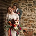 Newly weds, wife holding orange and dark pink bouquet, husband kissing the side of her tilted head