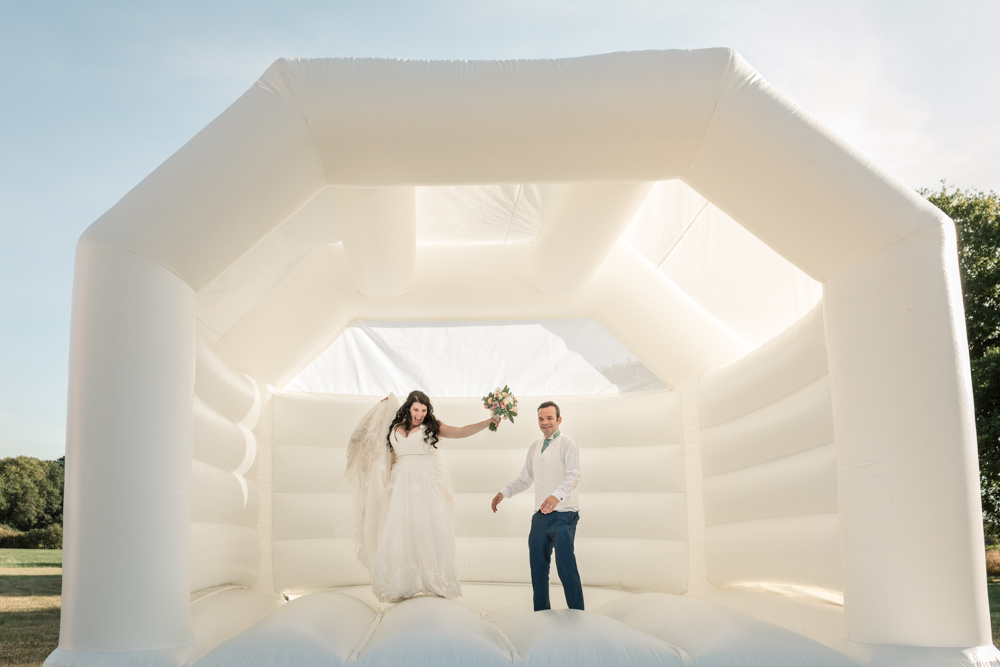 Newly wed couple jumping on a white bouncy castl