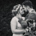 Black and white photo of a newly wed couple about to kiss