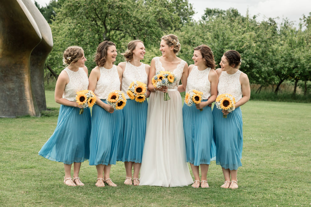 Bride outside on a lawn with 5 bridesmaids in turquoise skirts with cream tops