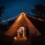 Tipi at night with fairy lights and people partying inside