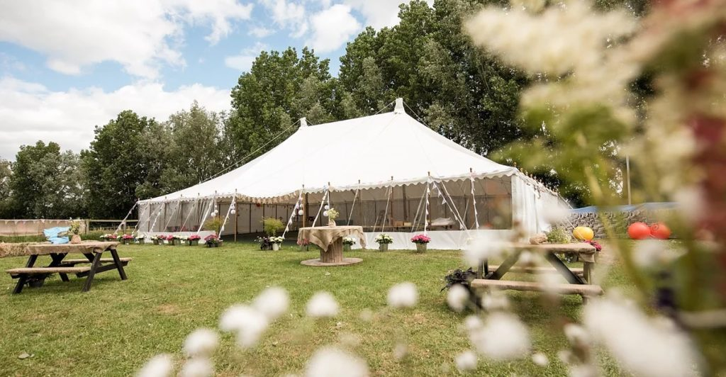 White big top type marquee in a field with trees behind